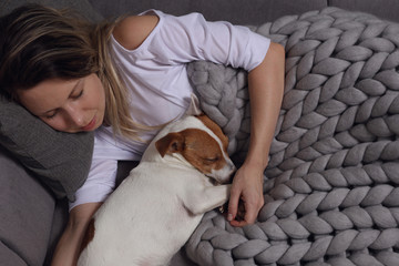 Woman and dog sleeping together. Covered with soft merino wool blanket