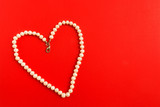 Heart shape of white pearl necklace on red background