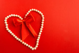 Heart of white pearl jewellery with red bow over red background