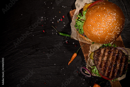 Top view of tasty burgers on wooden table. - 244612055