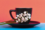 coffee in a black cup with a saucer, coral color background trend of 2019, lilies of the valley on the background of the cup