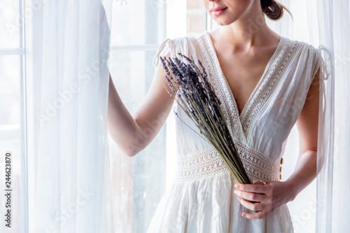Woman in white dress holding lavender in hands and stay near window. Image in high key style - 244623870