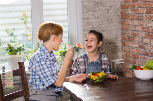 Poster Mom and daughter cook together at home