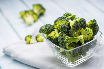 Fresh broccoli in bowl on kitchen table