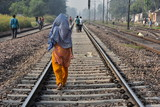 インドの首都のデリー 線路を歩く人々 サリーを着たインド人女性の後ろ姿