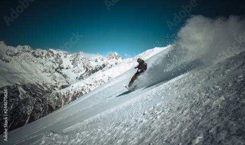 fototapeta na ścianę Snowboardzista jadący szybko w głębokim puchu i wzbijający firanę śniegu