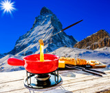 Fondue cheese, swiss winter ski holidays break for lunch, mountain view Matterhorn in Zermatt, Switzerland. - 244678408