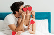 Young happy couple sitting on the bed, holding red hearts