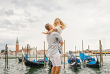 Young beautiful couple girl in a white dress a man in a white shirt walk near the water overlooking the Grand Canal in Venice Italy