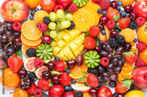 Healthy fruit platter background, strawberries raspberries oranges plums apples kiwis grapes blueberries mango persimmon, top view, selective focus - 244708262