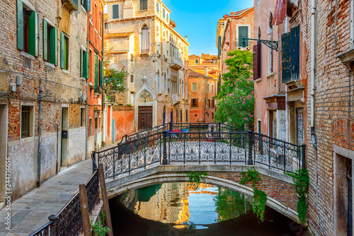 Narrow canal with bridge in Venice, Italy. Architecture and landmark of Venice. Cozy cityscape of Venice. - 244716656