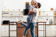 handsome boyfriend and attractive girlfriend hugging and standing in kitchen