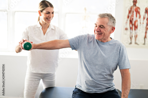 A Modern rehabilitation physiotherapy worker with senior client © pololia