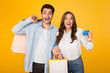 Attractive couple with shopping bags and credit card