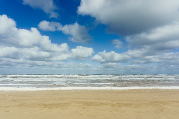 Beach with cloudy blue sky and waves at the sea background