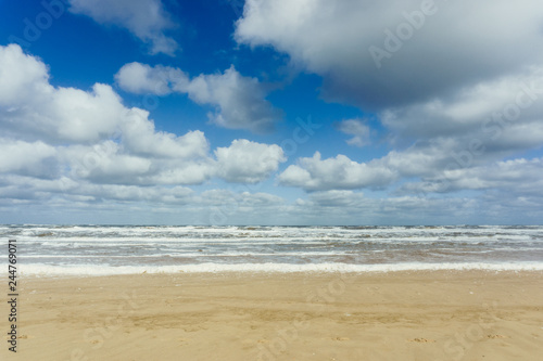 Beach with cloudy blue sky and waves at the sea background - 244769071