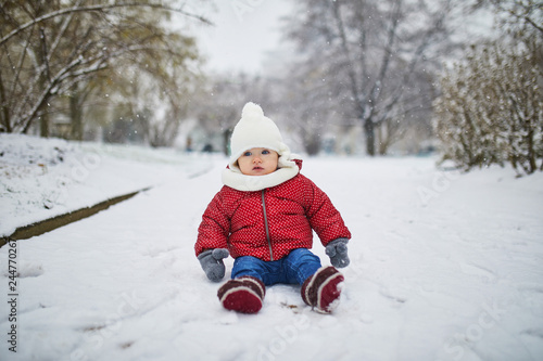 Wall mural Baby girl in stroller in Paris on a day with heavy snow