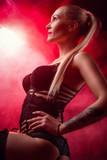 Damenunterwäsche, dessous, junge blonde Frau in erotischen Posen mit Nebel und rotem Licht