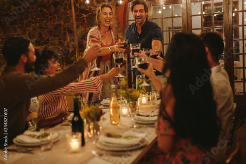 Group of friends toasting drinks at a party - 244827607