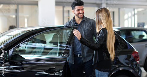 Young couple choosing new car for buying in dealership shop - 244831897