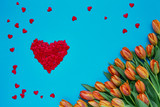 Fototapeta Tulipany - Valentines Day background. Orange tulips bouquet and red hearts on blue background. Top view, copy space. © Laima