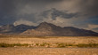Nevada Desert and Mountain Range - with a Thin Strip of Road in the Foreground, and a Long Stretch of Flat Land and Brush on a Cloudy, Overcast Day