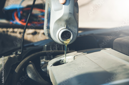 fototapeta na ścianę Auto mechanic is changing oil into a engine at car