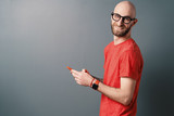 Cheerful hairless Caucasian man with beard, glasses, red T-shirt talking on the phone on gray studio background - 244901876
