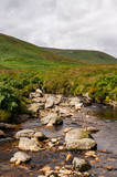 Dargle River passing through a green mountain valley in Wicklow, Ireland, near Maulin Peak. Water stream flowing through boulders and rocks.
