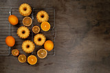 Small orange bundt cakes with fresh and dry oranges on cooling ruck, top view, flat lay
