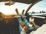 Woman drinking coffee paper cup inside car with feet warm socks on dashboard