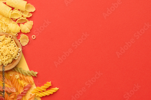 Various types of uncooked pasta on a orange background  top view. Place for text. - 244959076