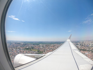 View from airplane window over airplane wing - flying over the city - travel concept