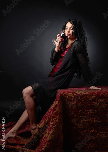 Portrait of attractive brunette with glass of red wine on a black background. - 244968224