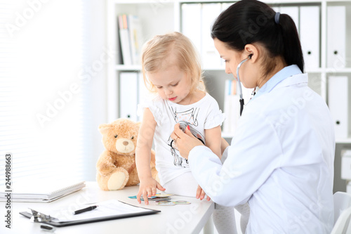 Leinwandbild Motiv Doctor and patient baby in hospital. Little girl is being examined by pediatrician with stethoscope. Health care, insurance and help concept
