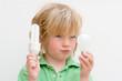 Leinwandbild Motiv Energy concept as boy holds conventional and energy saving lightbulbs