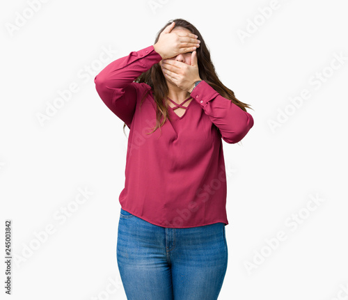 Leinwandbild Motiv Beautiful plus size young woman over isolated background Covering eyes and mouth with hands, surprised and shocked. Hiding emotion