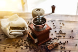 Manual coffee grinder on wooden table with sunny window behind - 245045222