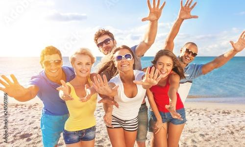 Leinwandbild Motiv Group of happy friends having fun together on the beach