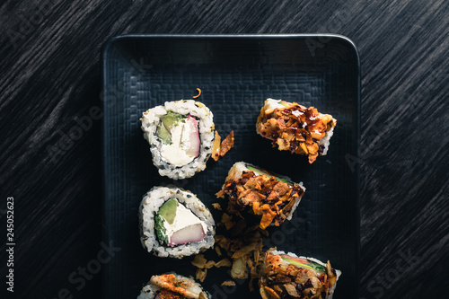 Sushi rolls on dark wood table.