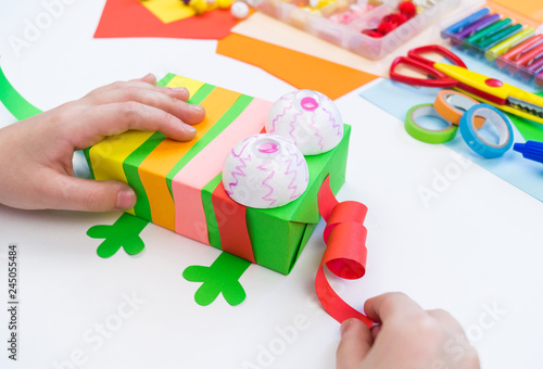 Child makes a hack box chameleon. Material for creativity on a white background.