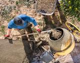 Workers pour concrete solution at a construction site - 245097264