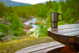 Picnic site table with thermal mug, norwegian mountains nature in the background. Camping with thermos.