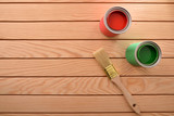 Two paint cans and brush on wooden slats top view - 245102437