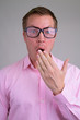 Face of surprised young nerd businessman with eyeglasses