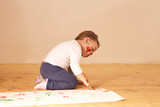 Little boy dressed in home clothes are sitting on the wooden floor in the room and painting with fingers on the paper