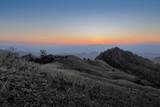 Fototapeta Zachód słońca - sunset at Doi Samur Dao, mountain view evening of green hill and forest cover with soft mist with yellow sun light in the sky background, Sri Nan National Park, Nan province, Thailand. © Yuttana Joe