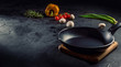 Empty pan on dark table surrounded by vegetarian cuisine ingredients