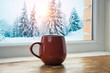 Leinwandbild Motiv Winter background - cup with candy cane, woolen scarf and gloves on windowsill and winter scene outdoors. Still life with concept of spending winter time at cozy home with cold weather outdoors
