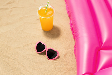 vacation and summer holidays concept - pink sunglasses, orange juice and swimming mattress on beach sand